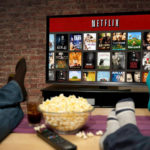 A TV screen showing Netflix and movie titles