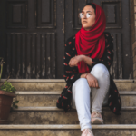 Photo by M.T ElGassier on Unsplash. [Image description: Woman wears a hijab and sits on a set of steps outside.]