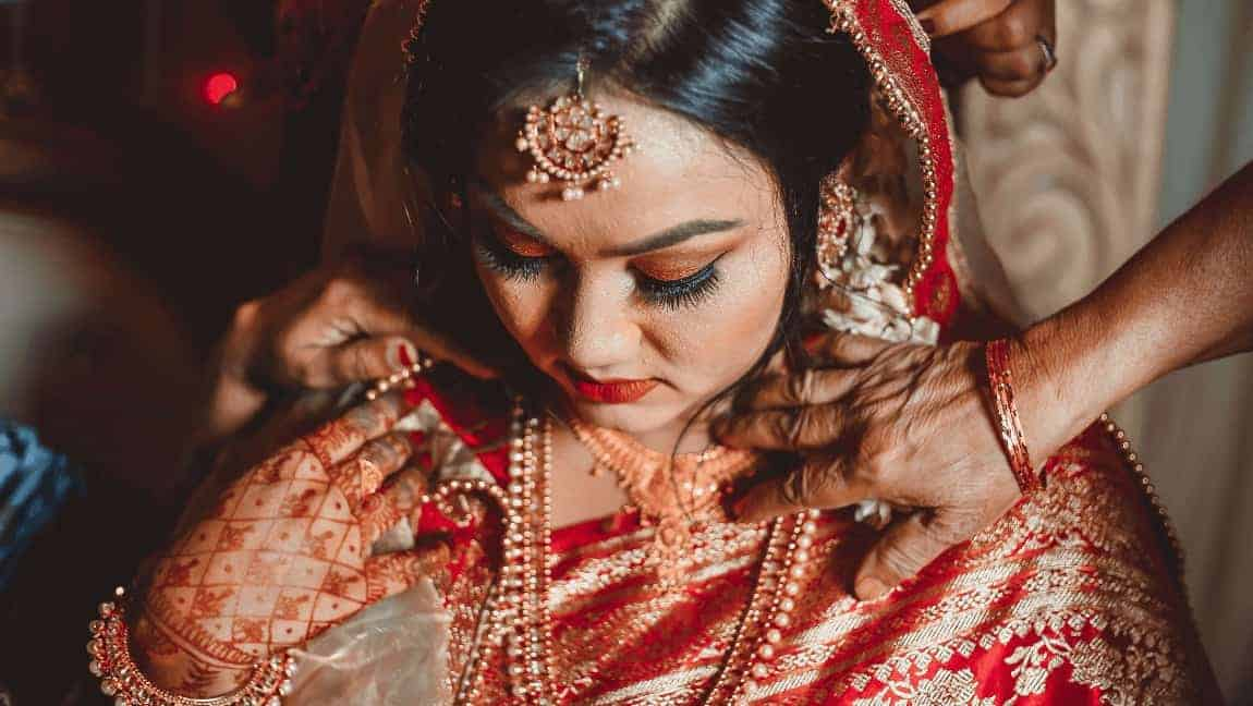 [Image description: Bride looks down, hands on her shoulders.] Photo by SadMan Chowdhury from Pexels