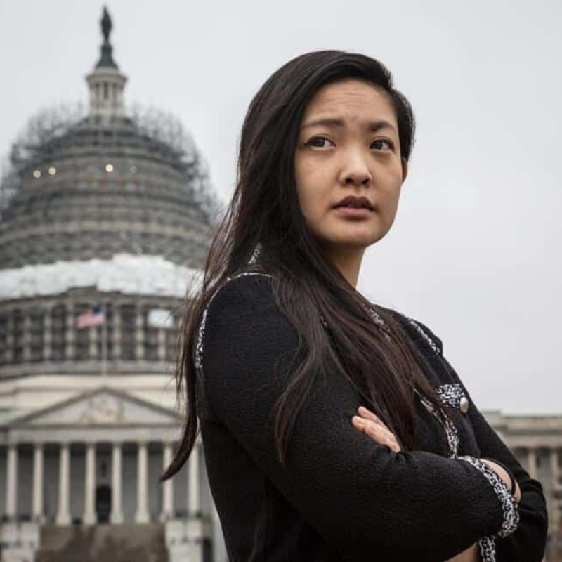 [Image description: Amanda Nguyen stands in front of the Capitol, arms crossed.] Photo via The Boston Globe