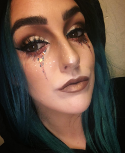 woman with extremely detailed glitter tear makeup