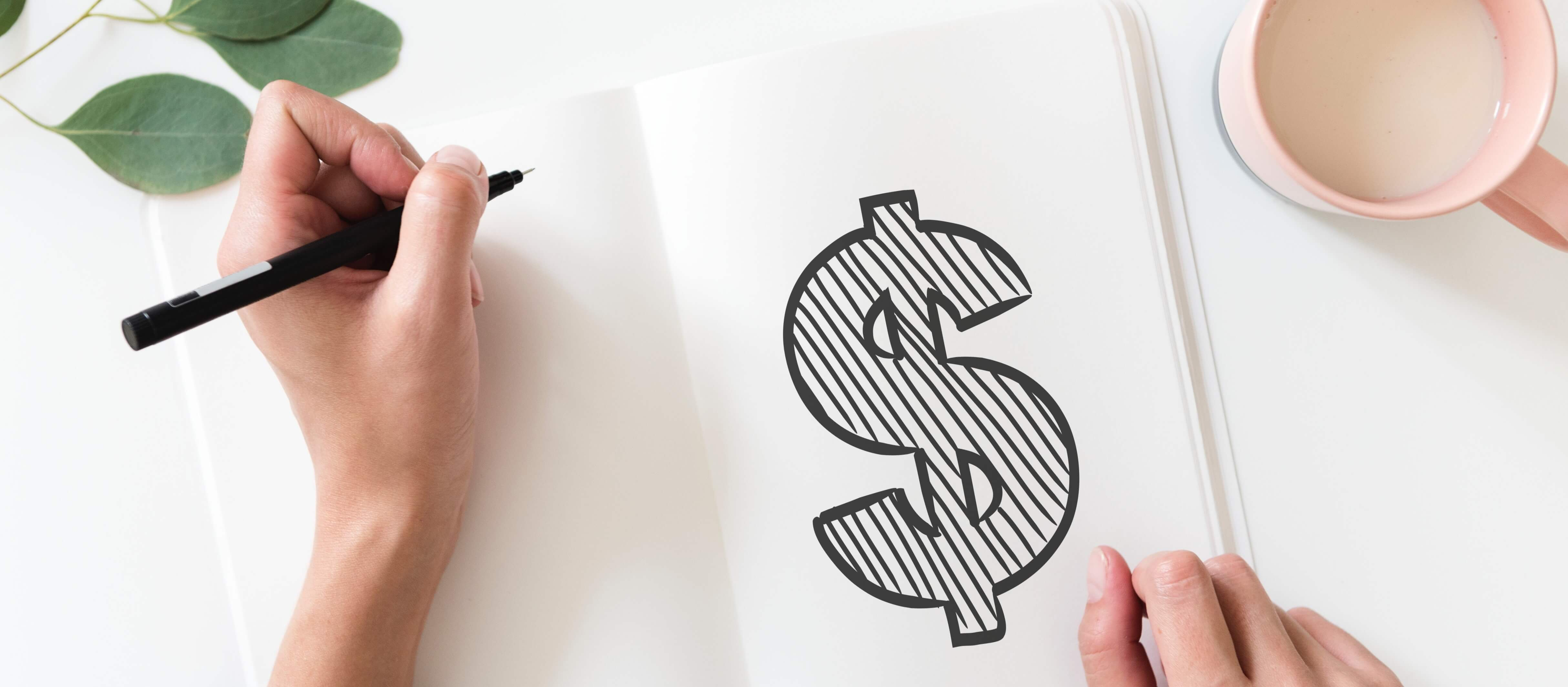 Image description: hands are viewed from above, on a notebook, a large dollar sign has been drawn in black marker.