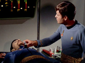 Dr McCoy using a tricorder for a diagnosis