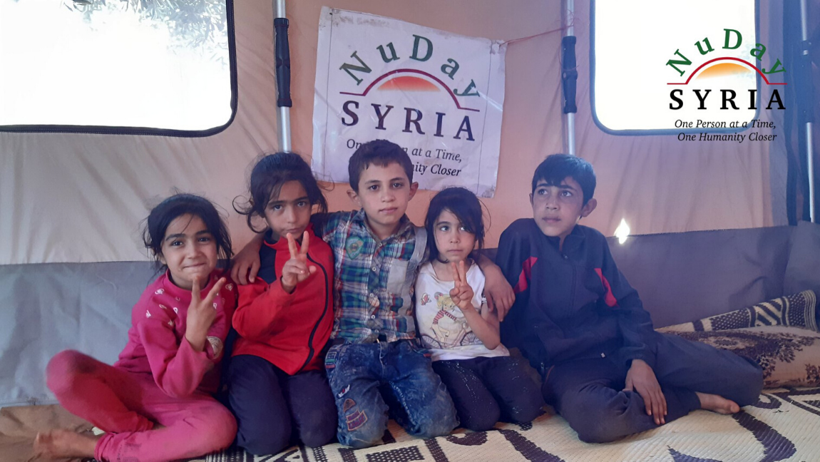 [Image description: Group of children sit in front of a NuDay Syria sign.] via NuDay