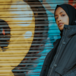 [IImage description: Woman wearing a headscarf and winter jacket stands in front of a graffitied door.] via Brunel Johnson on Unsplash