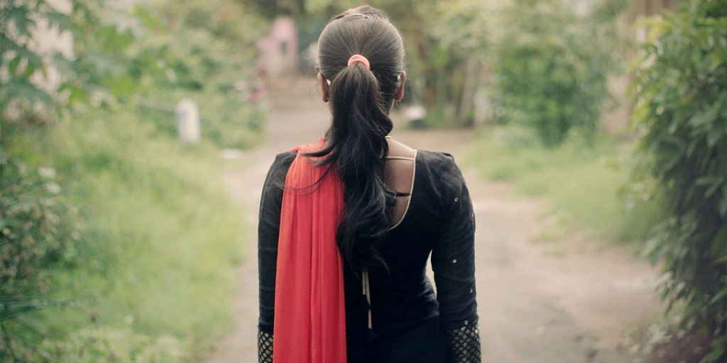 We see the back of a pony-tailed girl in a black top and a red dupatta. She is standing in front of an empty dirt road.