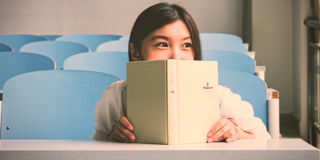 A young girl is sat at a table, leaning low and hiding half her face behind an open book.