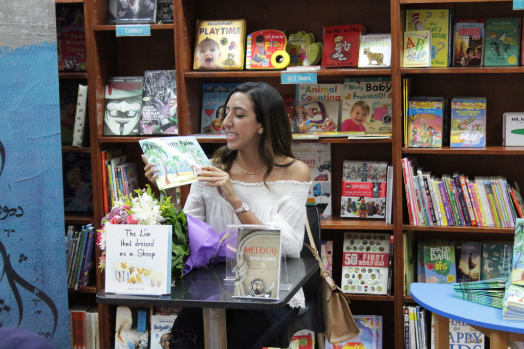 "Image shows Dina at a signing even in a bookshop, holding her book ""The Lion Who Dressed as a Sheep"""