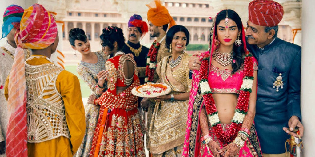 [Image description: A group of people stand at a wedding.] via Vogue India