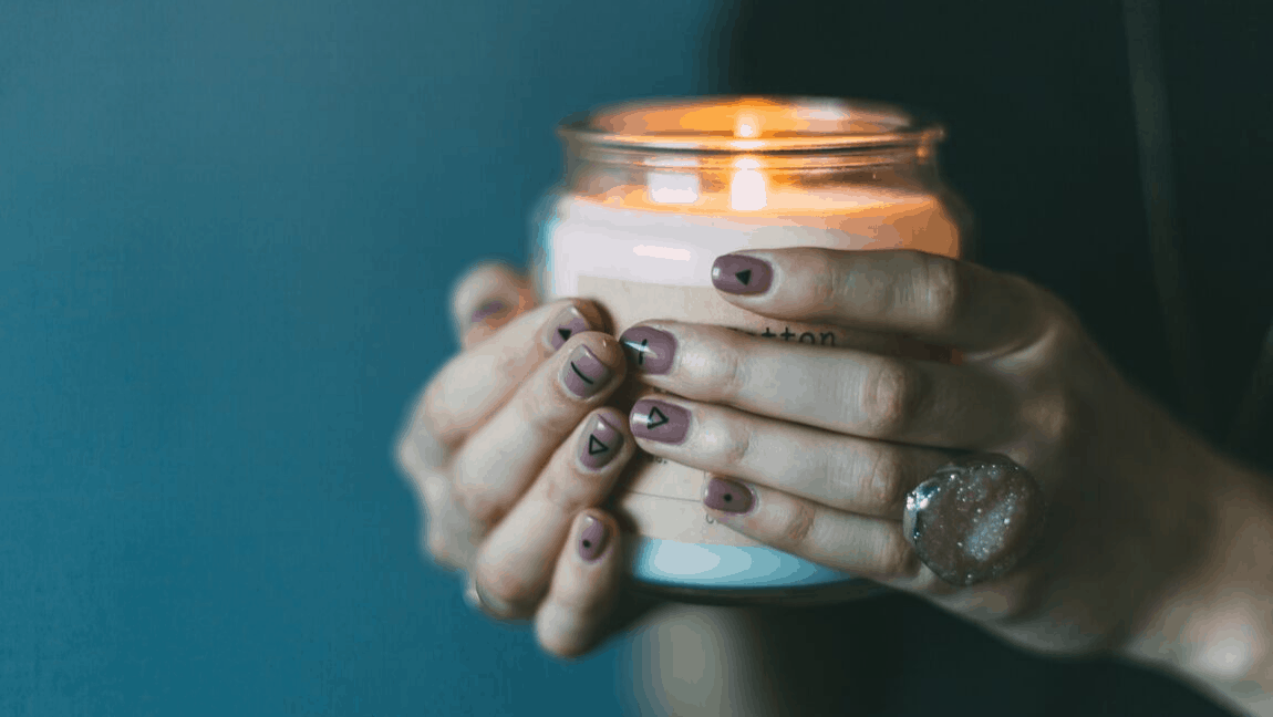 [Image description: Hands with painted nails, holding a lit candle] Photo by Daiga Ellaby on Unsplash