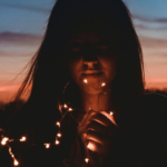 Sunset background with a girl in front with fairy lights