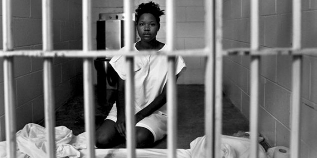 A black woman sitting behind a jail cell.