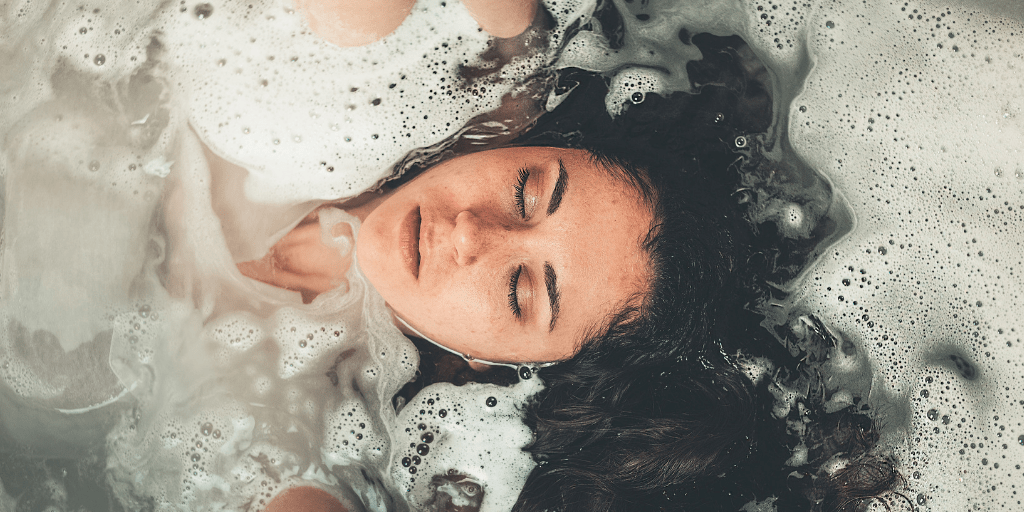 [Image description: Girl lays in bathwater, eyes closed.] Photo by Craig Adderley from Pexels