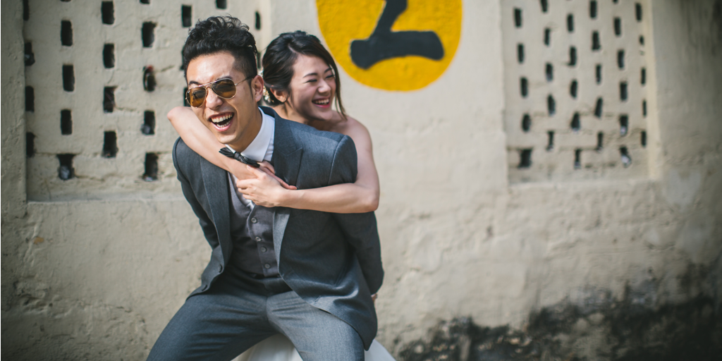 Asian girl in a white wedding dress with her arms tightened around Asian man in a gray suit and sunglasses. Both are laughing in the picture.