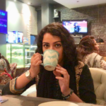 Community Fellow Arsh Khan sitting on a sofa chair in Jade cafe. She's sipping from a blue patterned mug. There is a painting of a lady on a red brick wall in the background.