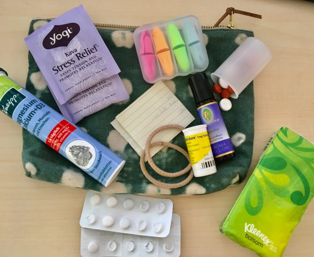 An assortment of items in the authors mental health kit, on top of a small pouch assembled on a desk.