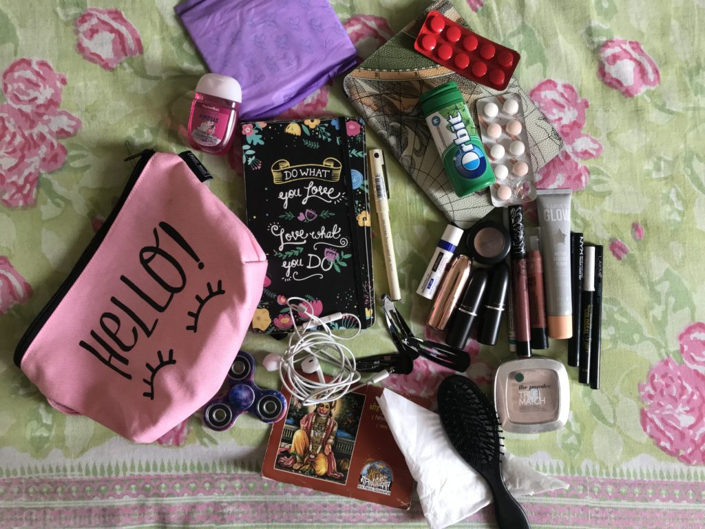 Small pink pouch with it's contents spilled out on a floral sheet. Various personal care items, medications, makeup, a kindle are visible.