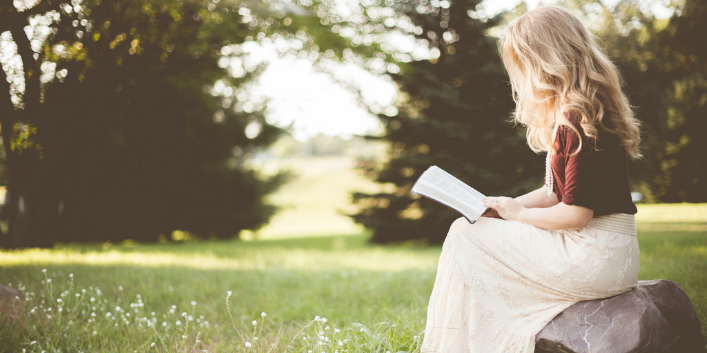 Woman sitting on a bench outside reading a book