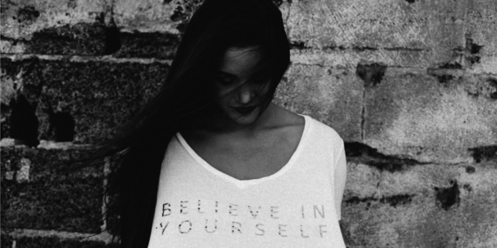 "Black woman wearing a shirt that says ""believe in yourself"""