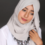 A girl looking down and smiling wearing a grey hijab.