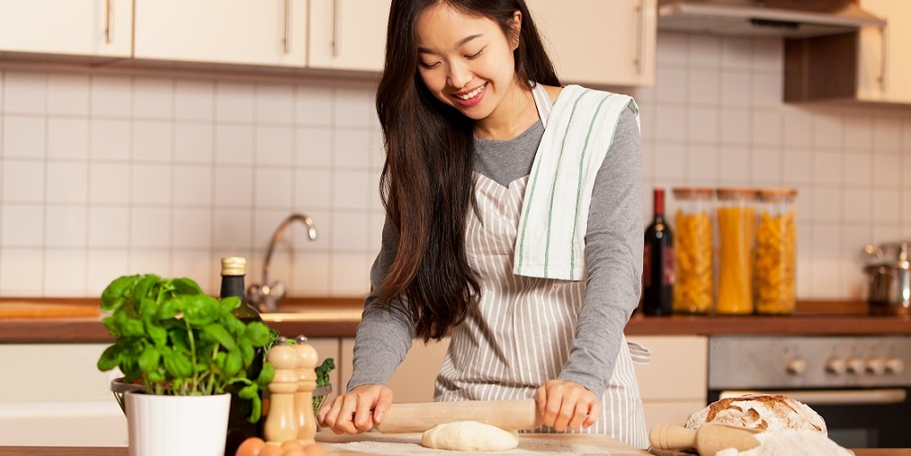 [Image Description: Asian woman is baking in her home kitchen.]