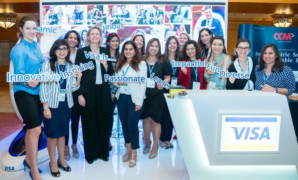 A group of women from VISA holding different signs with text: VISA is, innovation, fun, passionate, leader, diverse, impactful. They are standing on a VISA stand.