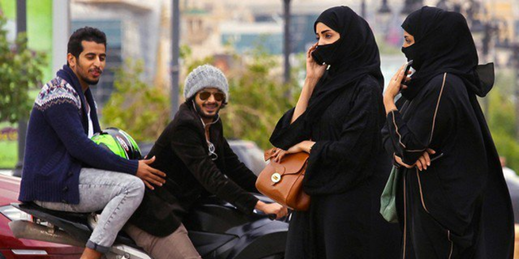 Men checking out two women wearing burqas