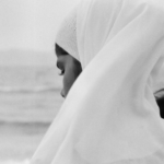 [Image Description: A woman standing with her head covered, near a water body.]