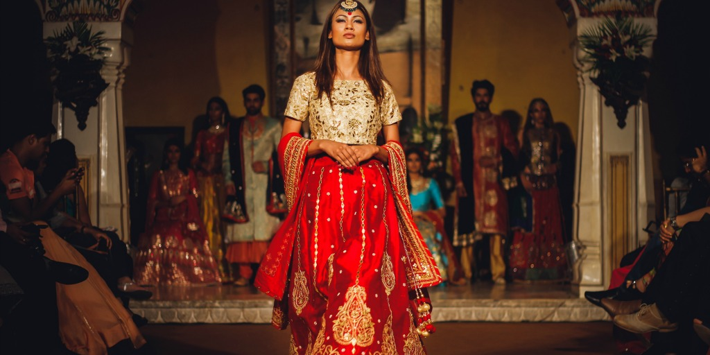 [Image Description: Woman in Indian clothing strutting away from others in the background.]
