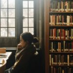 [Image Description: A woman sitting in a library.]