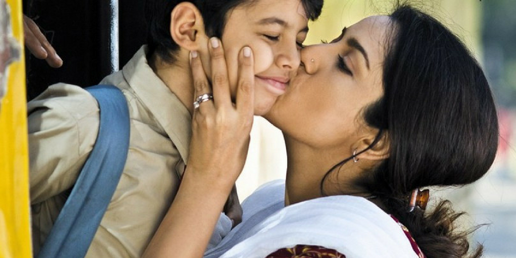 [Image Description: A woman kissing her son on the cheek.]