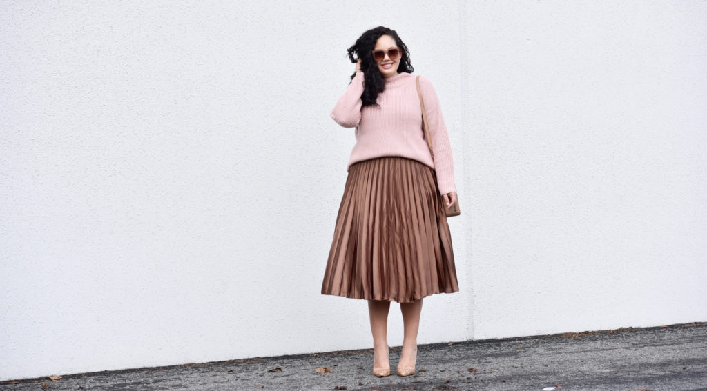 Image shows Tanesha in a bronze midi skirt, nude heels, pink sweater and sunglasses.