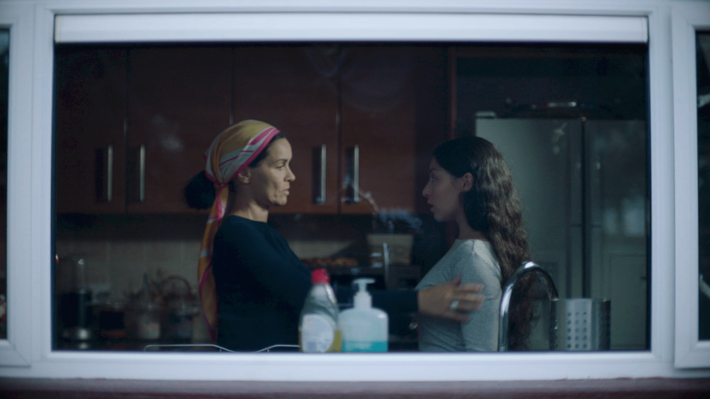 Image shows a still from the short film, Daughter. Sara's mother stands in a kitchen, her hand is resting on the upper arm of her android daughter, who stares blankly ahead.