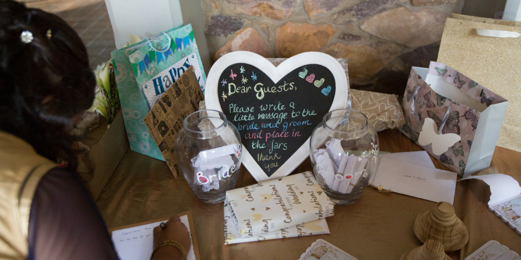 "[Image description: A table with presents, some wrapped and some in bags, lie on a table covered with a brown tablecloth. A woman is leaning down to write a message on a piece of paper. At the center of the table is a heart-shaped chalkboard that reads, ""Dear Guests, Please write a little message to the bride and groom and place in the jars. Thank you.""]"
