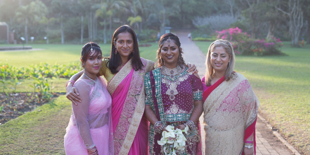 [Image description: a photography of the author with her bridesmaids. The author is wearing a purple and green lengha and her bridesmaids are wearing sarees in different shades of pink. There is an expansive garden in the background and the light is hazy from the sunset. Everyone is smiling.]