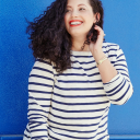 Image shows Tanesha Aswathi against a blue wall, wearing jeans and a striped shirt.