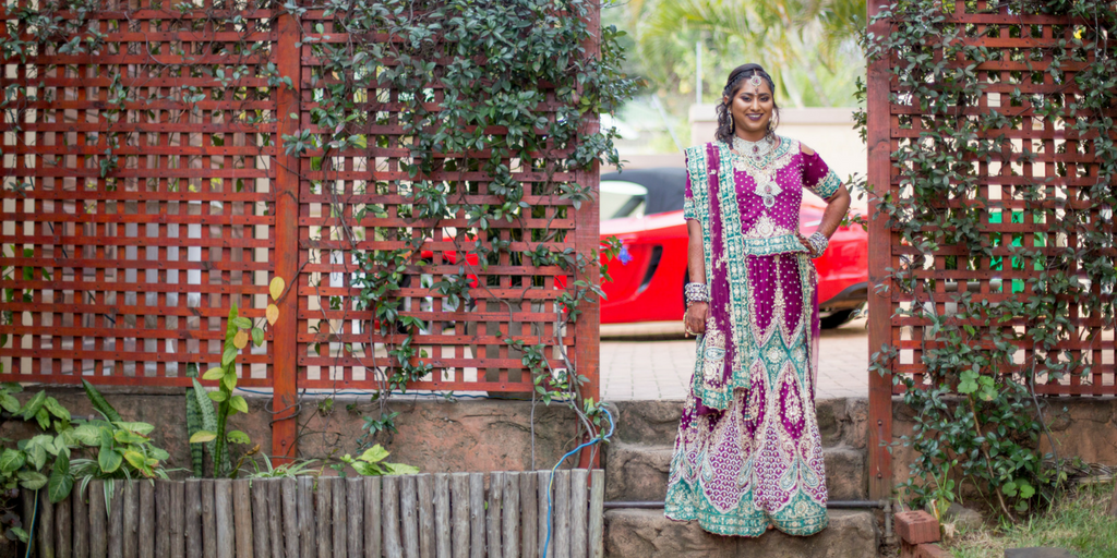 [Image description: a photograph of Ariana, the author, standing in a heavily beaded green and purple lengha. There are two trellises on either side of her that are covered in jasmine creepers.]