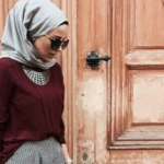 [Image Description: A woman wearing hijab and sunglasses and looking down, standing in front of a wooden door.]