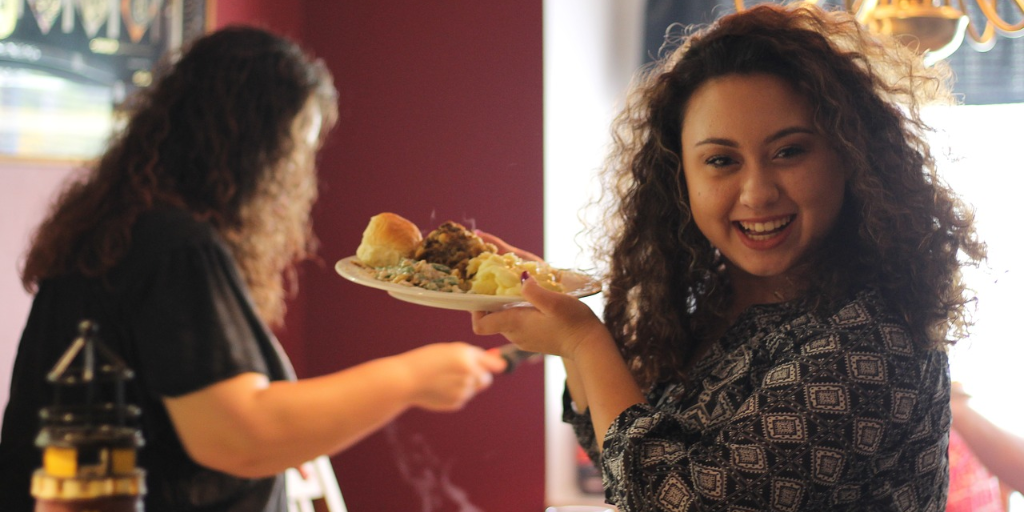 Woman looking in to the camera smiling and holding a plate of food with another woman getting a plate of food in the background
