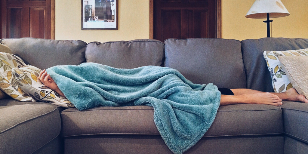 [Image Description: A person sleeping on the couch with a blanket.]