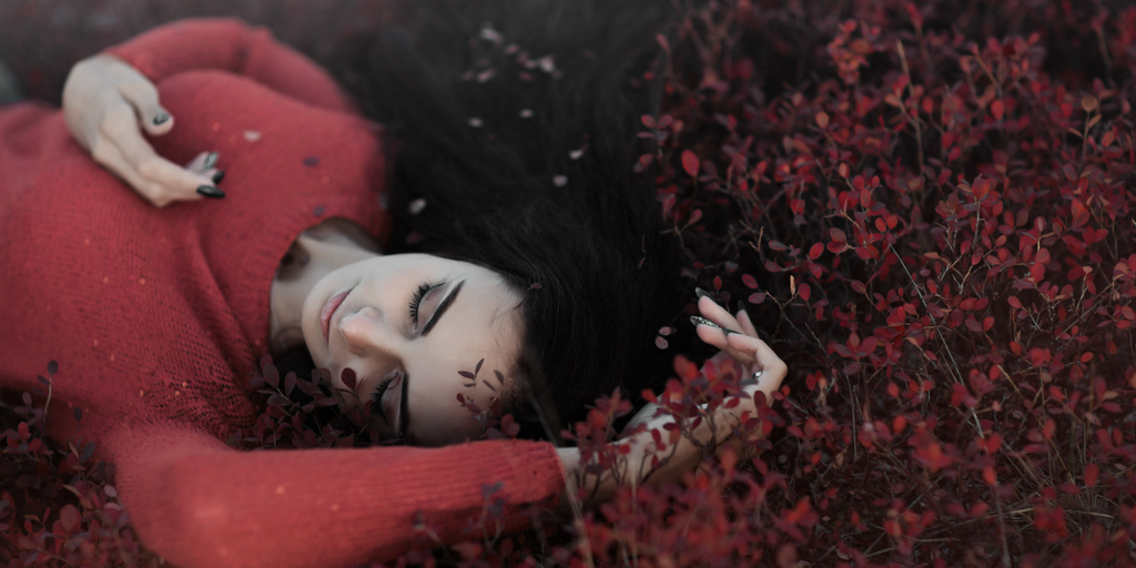 [Image Description: A girl is lying on the ground wearing a red top near branches of small red flowers with her eyes closed and her hand touching the flowers.]