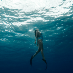 [Image Description: A woman swimming underwater looking up to the surface.]