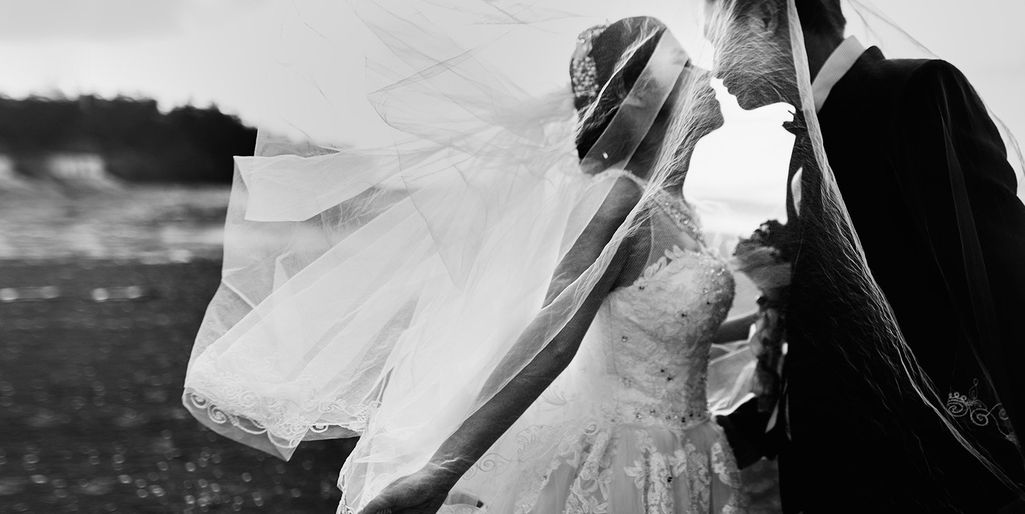 Image description: A black-and-white photo of a woman and a man on their wedding day. The woman's veil is blowing elegantly in the wind and they look very much in love.