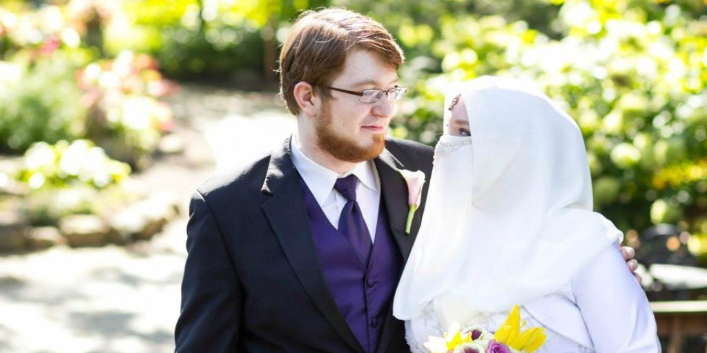 A light skinned red haired man in a suit stands next to a light skinned woman in a Burqa on their wedding day