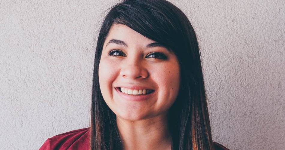 A head shot of Reyna Montoya is grinning at the camera. The background is a coarse textured white wall.