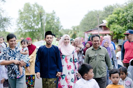 [Image description: A couple are walking hand-in-hand on a road while their families walk alongside them. Everyone is dressed informally, while the bride and groom are wearing more traditional clothing. There is a blurry building in the background and a few green trees. From Pinterest]