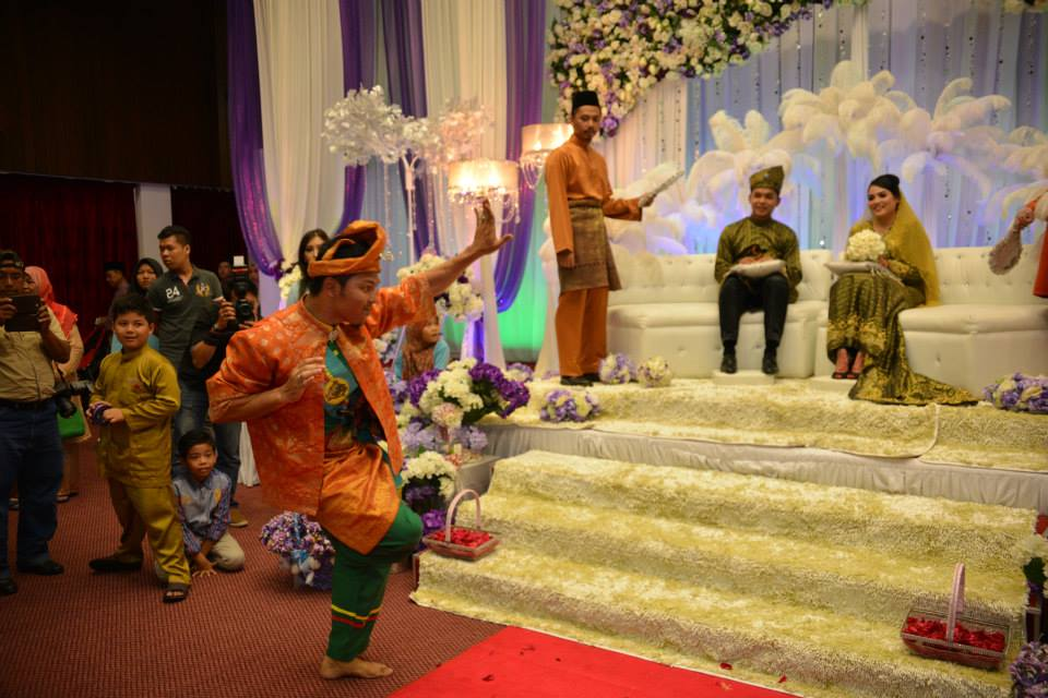 [Image description: A Malaysian bride and groom sit on their wedding throne while watching a Silat performer. He is wearing an orange, traditional outfit, raising his left hand and right leg. Guests mill around the scene. From kahwinmall.com]