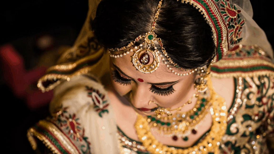 [Image description: Woman in bridal makeup and dress looks down.] via pixabay.com