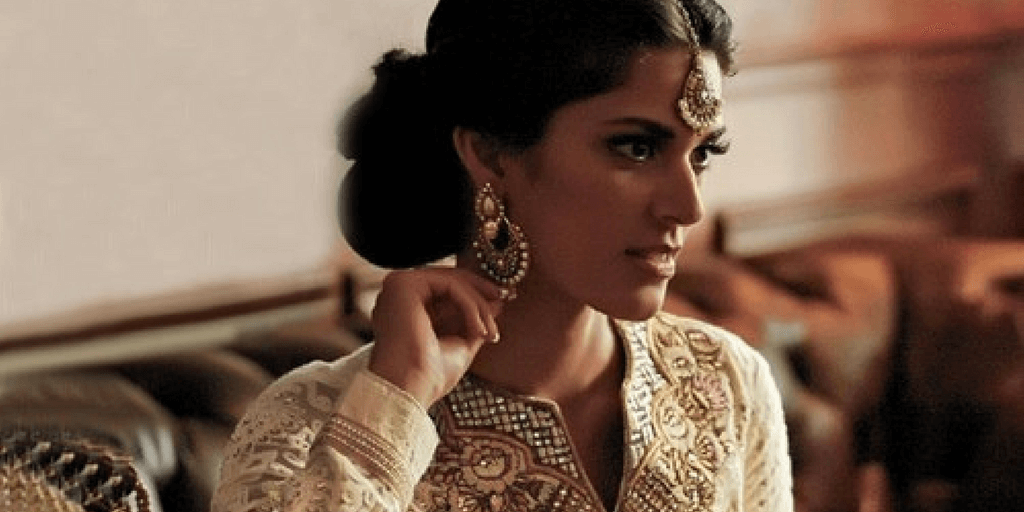 A South-Asian woman in a traditional attire facing the ride side while touching her earring.