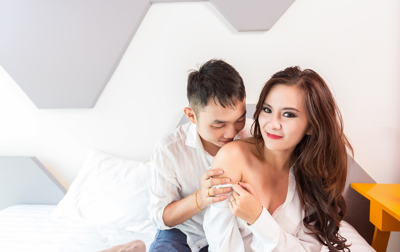 Asian man and woman in bed. The woman's shirt is pulled off her shoulder and the man is kissing her exposed shoulder.